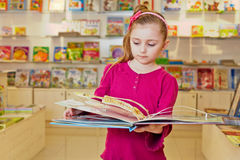Little girl views fold-out book on anatomy. In book department at store Stock Photography