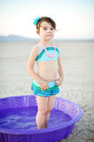 Little Girl Vintage Bathing Suit in Plastic Pool. Little girl in vintage style bathing suit standing in a purple plastic pool in the middle of the desert Royalty Free Stock Photography
