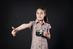 Little girl with vintage camera thumb up at black background Stock Photography