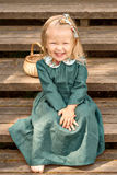 little girl in vintage retro linen dress barefoot sitting and laughing on a wooden stairs in the park with Wicker basket stock images