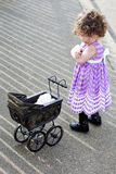 Little girl with vintage stroller looking upset Royalty Free Stock Image