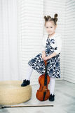 Little girl with a violin and fiddlestick. Little girl with a violin and bow, looking at camera Stock Photos