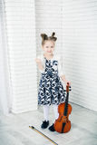 Little girl with a violin threatens fist stock photos