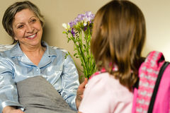 Little girl visiting her ill grandmother Stock Photography