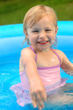 Little Girl in Wading Pool. A pretty little girl (almost 3 years old) outside in a wading pool, wearing a pink swimsuit Stock Photos