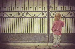 Little girl waiting alone at the gate. Anxious Little girl waiting alone at the gate for her mother Royalty Free Stock Images