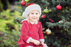Little girl waiting for a Christmas in the wood. Christmas in juli. Stock Photography