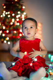 Little girl waiting for her first xmas gift. In front of the Christmas tree royalty free stock images