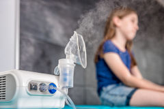 Little girl waiting for medical inhalation treatment with a nebu. Lizer at the hospital Stock Photos