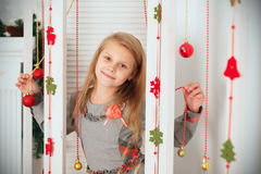 Little girl waiting for a miracle in Christmas decorations Stock Image