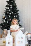 Little girl waiting for a miracle in Christmas decorations Stock Images