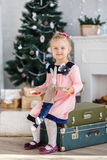 Little girl waiting for a miracle in Christmas decorations Stock Photos