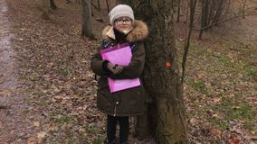 Little girl waiting near tree for friend stock video footage