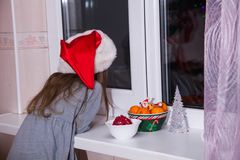 Little girl waiting Santa Claus magic Christmas window winter dark tangerine tale. Little girl waiting for Santa Claus. Waiting for magic Christmas and looks out Stock Photos
