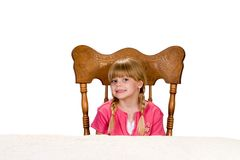 Little girl waiting at table. Portrait of a beautiful young little Caucasian girl sitting on a big wooden chair and waiting at the table. Image isolated on white Royalty Free Stock Images
