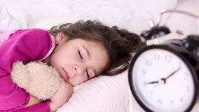 Little girl wakes up, alarm clock close up stock footage