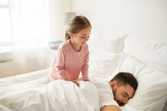 Little girl waking her sleeping father up in bed Royalty Free Stock Images