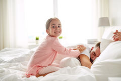 Little girl waking her sleeping father up in bed Stock Images