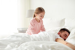Little girl waking her sleeping father up in bed Stock Photos