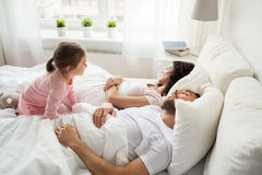 Little girl waking her sleeping parents up in bed Royalty Free Stock Image