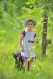 Little girl on walk in forest looks up Stock Photos