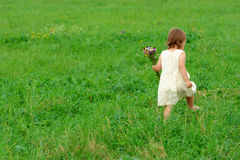 Little girl walk on green field Stock Images