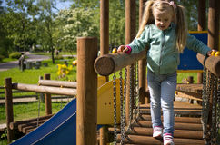 Little girl walk on outdoor slide. A cute little four year old girl walk in logs of outdoor fun slide construction Stock Photo