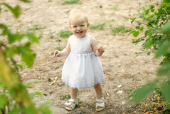 Little girl for a walk in the park. Summer day Stock Photos