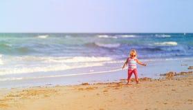 Little girl walk on sand beach Stock Image