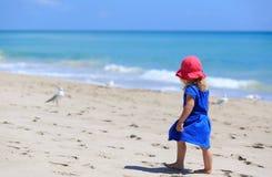 Little girl walk on sand beach Stock Photos