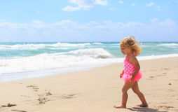 Little girl walk on sand beach Stock Photography