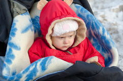 The little girl on a walk in the stroller. In the winter Royalty Free Stock Photography
