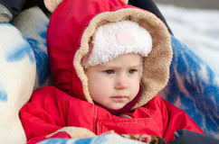 The little girl on a walk in the stroller. In the winter Stock Photo