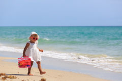 Little girl walk with toys on sand beach Royalty Free Stock Photography
