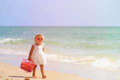 Little girl walk with toys on sand beach Stock Image