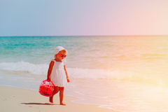 Little girl walk with toys on sand beach Stock Photo