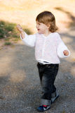 Little Girl Walking. Beautiful little girl in white jacket and jeans showing something she just found stock photos