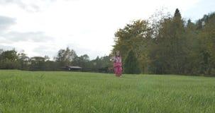 Little girl walking across the meadow toward stock video footage
