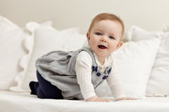 Little girl walking all fours on bed Royalty Free Stock Image