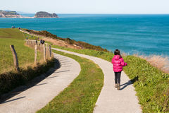 Little girl walking along a path by the sea Royalty Free Stock Photo