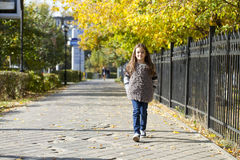 Little girl walking on autumn street Royalty Free Stock Photography