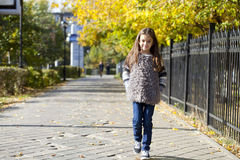 Little girl walking on autumn street Royalty Free Stock Image