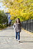 Little girl walking on autumn street Stock Photo