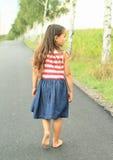 Little girl walking barefoot on asphalt street Stock Image