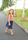 Little girl walking barefoot on asphalt street Royalty Free Stock Photo