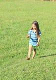 Little girl walking barefoot Stock Photo