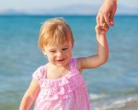Little girl walking on the beach Stock Photo