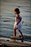 Little Girl Walking on Beach Stock Images