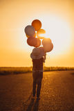 Little girl walking with colorful balloons on road in field at sunset. Summer freedom and travel. Hope concept. Stock Image