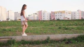 Little girl walking on concrete log on urban wasteland stock video